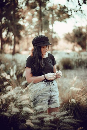 Young woman wearing hat while standing on land