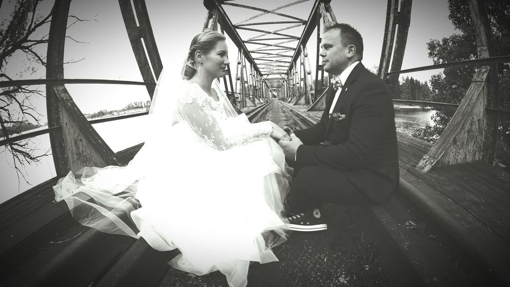 Just married. Independent Two People Love Togetherness Lifestyles Real People Sitting Enjoyment Fun Men Young Adult Celebration Holding Day Young Women Outdoors Wedding Married Marriage  Masuria In Polish Suit Old Metal Bridges Sitting Bleck & White Portrait Lake Village