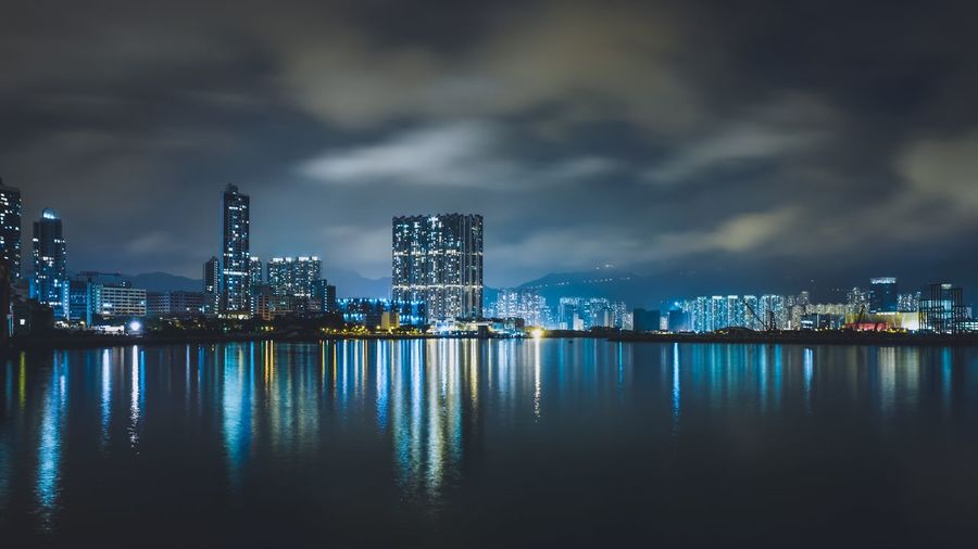 Reflection Of Blue Illuminated Buildings In River Against Sky At Night