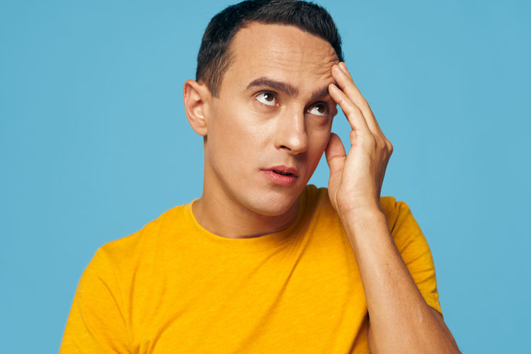 Man looking away against blue background