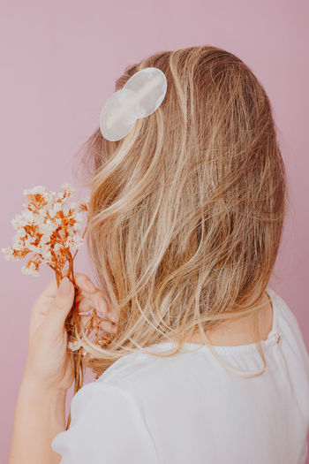 Rear view of woman with pink flower against white background