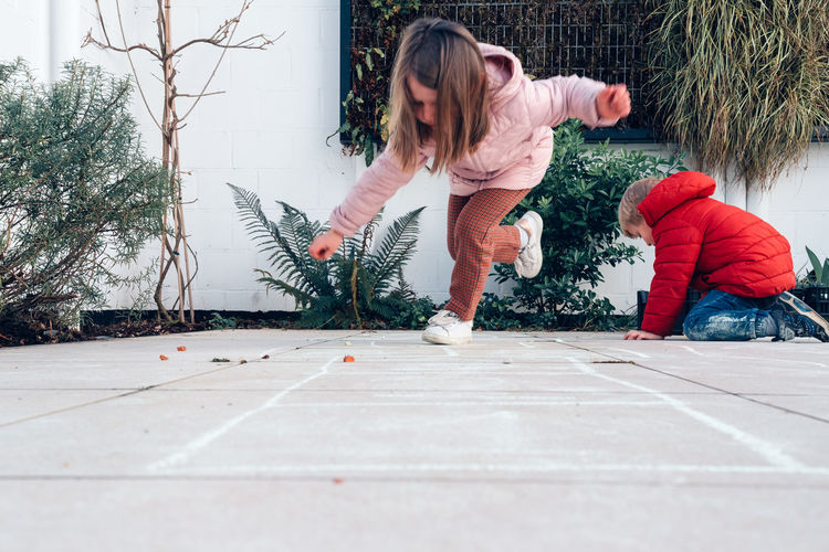 Children playing hopscotch in a terrace outdoors - leisure time