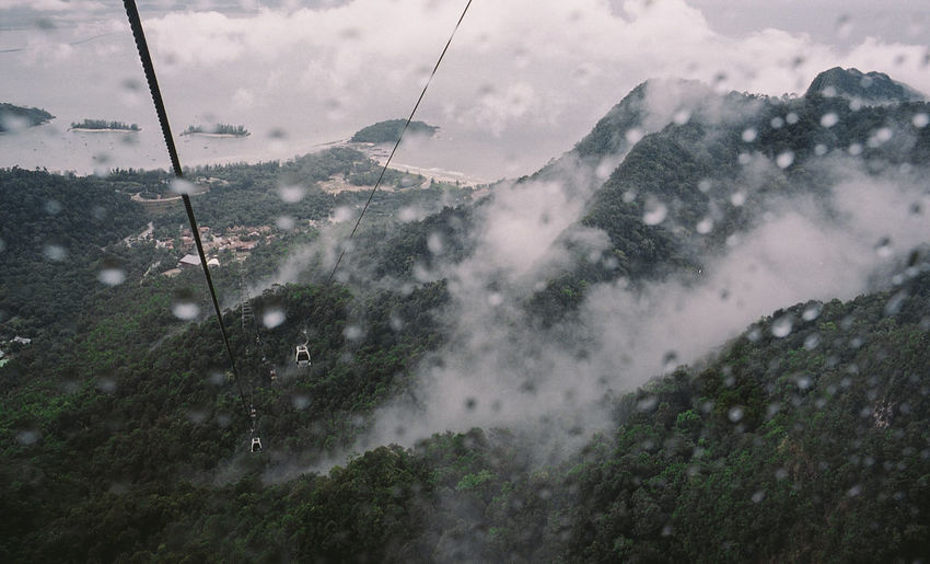 Overhead cable car over mountains seen through wet window