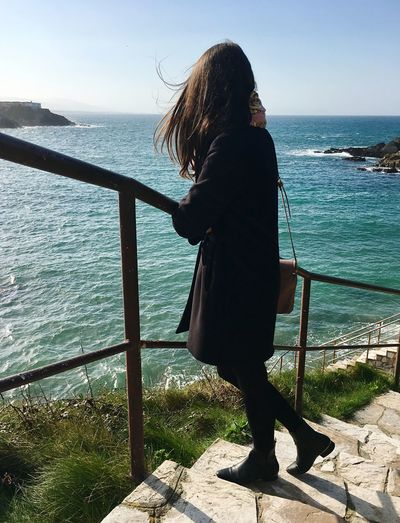 Full length of woman standing on steps against sea at tapia de casariego