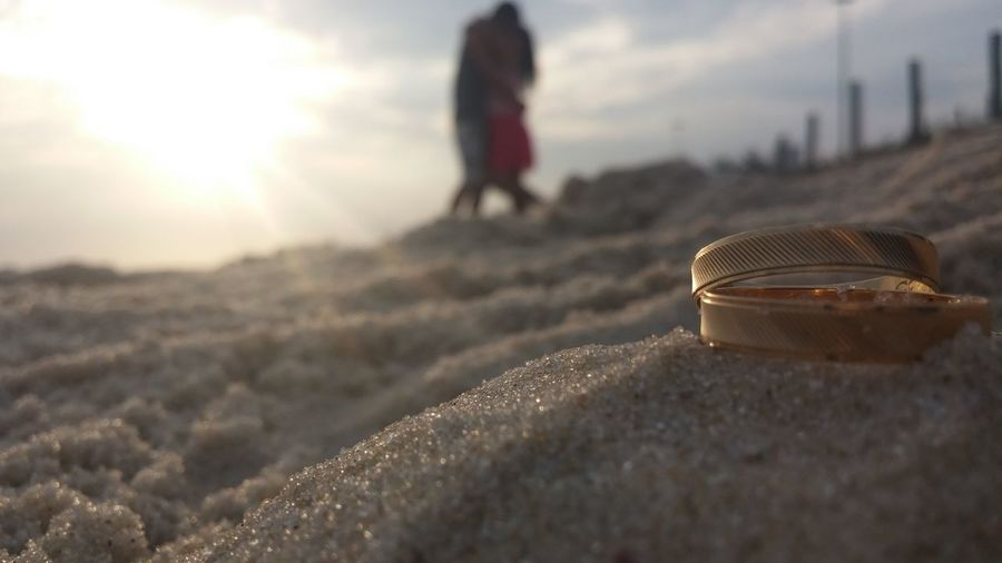 Close-up of wedding rings on sand with couple in background