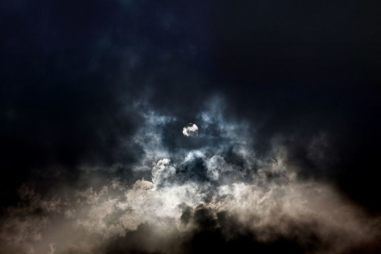 Sun through clouds on a windy day. Sky Cloud - Sky Nature Beauty In Nature No People Low Angle View Dark Outdoors Scenics - Nature Illuminated Black Color Copy Space Cloud Clouds And Sky Sun Sunlight darkness and light