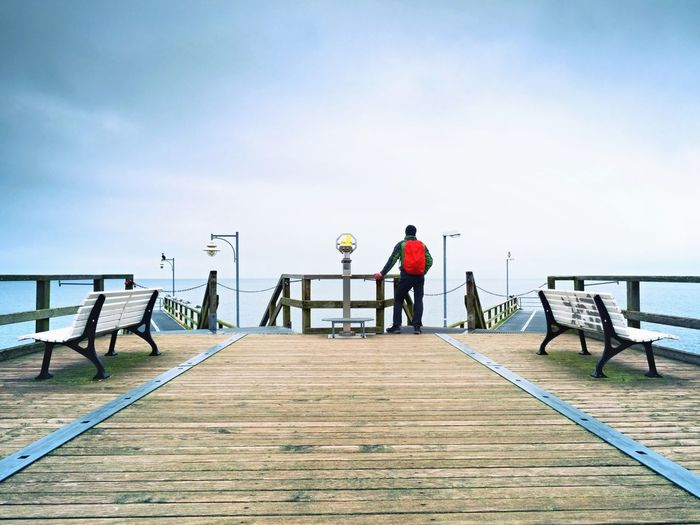 Tourist with red backpack on wooden pier above sea. man in trekking suit in harbor in rainy day