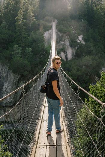 Portrait of man standing on footbridge in forest