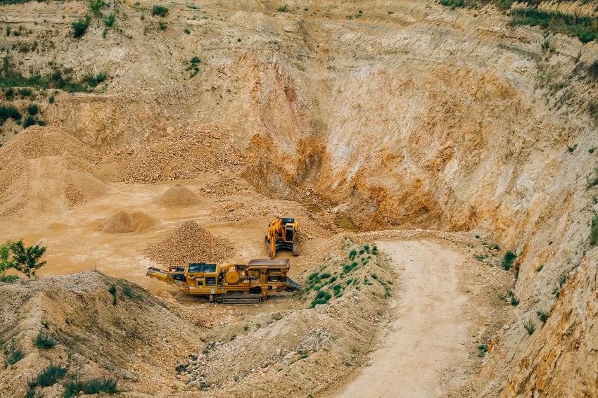 Minerals Bulldozer Commercial Land Vehicle Construction Industry Construction Machinery Construction Vehicle Earth Mover Environment Geology High Angle View Industrial Equipment Industry Land Vehicle Landscape Machinery Mine Mining Mode Of Transportation Quarry Road Stone Surface Mine Transportation Truck Vehicle