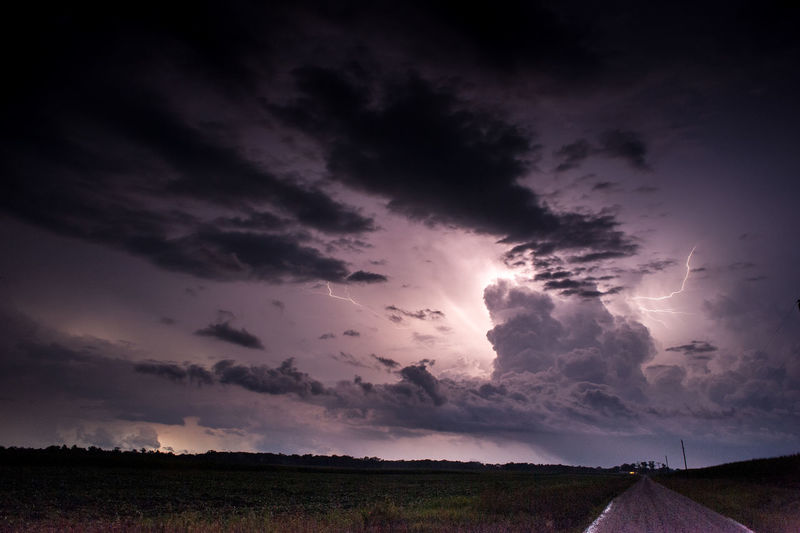 Road amidst field against lightning at night