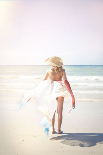 Woman With Textile Wearing Hat While Standing At Beach Against Clear Sky During Sunny Day