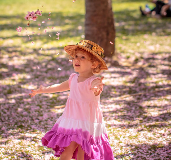 A young girl throws cherry blossom petals in the air at the Brooklyn Botanical Garden. Brooklyn Botanical Garden Cherry Blossoms Childhood Cute Elementary Age Flower Flower Girl Focus On Foreground Grass Happiness Hat Innocence Nature One Person Outdoors Petal Pink Color Pink Dress Portrait Sun Hat Throw Young Young Girl