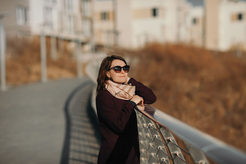 Portrait of woman standing by railing in city