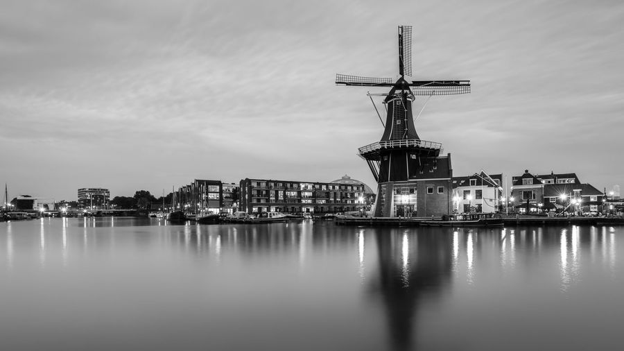 River with windmill against the sky