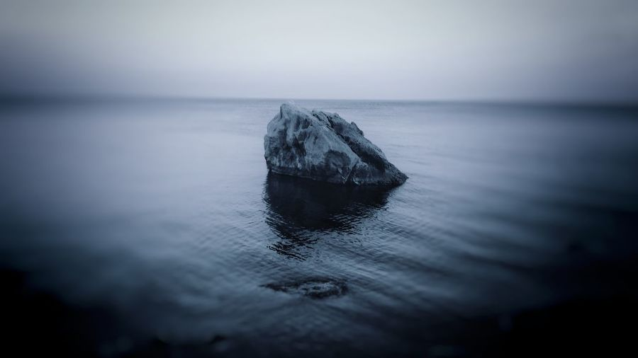Desolate rock standing in the sea Serenity Vignette Softness Soft Waves Edge Blur Desolate Rock - Object Monochrome Blue Dusk Water Sea Wave Beach Sunset Sky Horizon Over Water Close-up Seascape Rippled Calm Atmospheric Mood Waterfront Water Surface