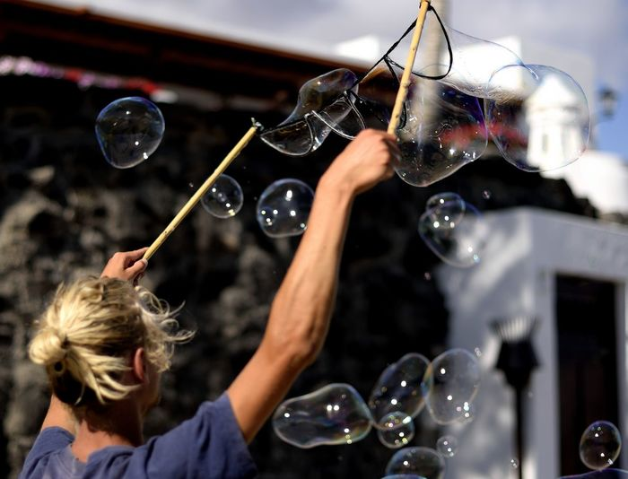 message in a bubble Bubble Bubble Wand Day Focus On Foreground Fragility Indoors  Leisure Activity Lifestyles Men Mid-air Motion People Playing Real People Soap Sud Transparent Two People Women