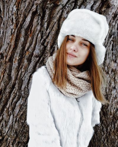 Portrait of woman in snow covered tree trunk during winter