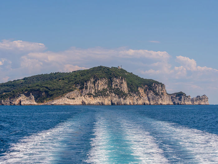 View from a motor boat leaving behind a mountainous island covered by a green forest