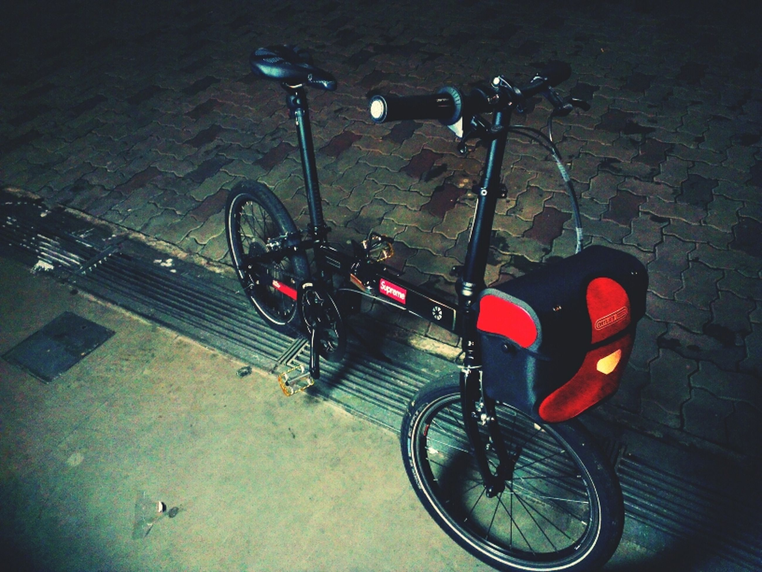 transportation, high angle view, mode of transport, night, land vehicle, illuminated, street, red, no people, road, outdoors, car, stationary, close-up, street light, bicycle, lighting equipment, absence, parking