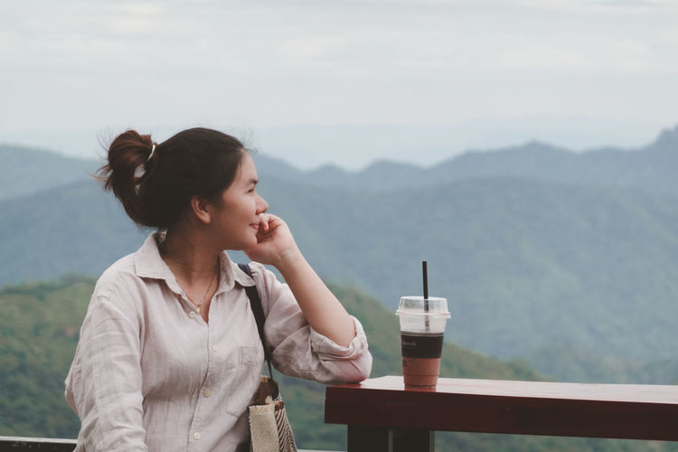 Woman looking at camera on table against mountains