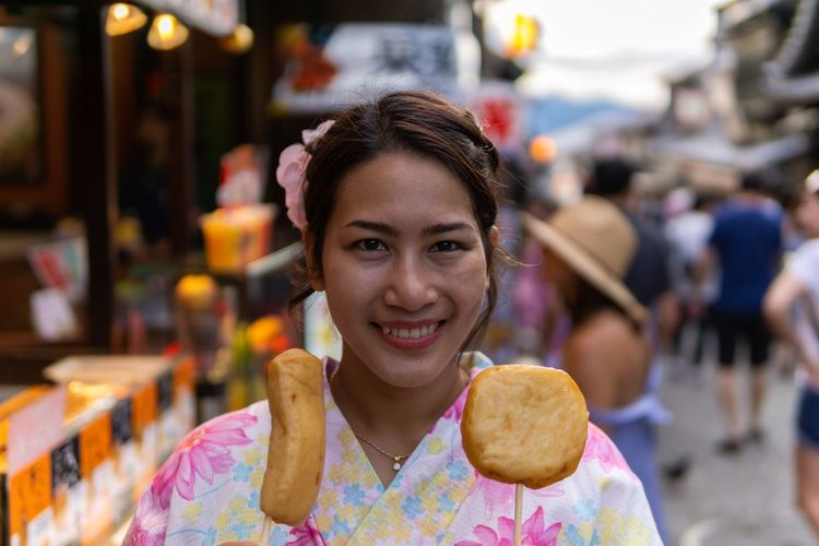 Portrait of smiling young woman holding food while standing on street in city