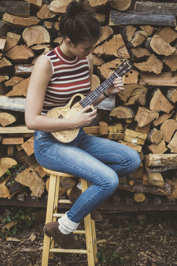 Young woman sits on a stool in front of a woodpile playing the ukulele Beautiful Music Sitting Woman Brunette Cabin Casual Clothing Day Full Length Girl Leisure Activity Lifestyles Log Musical Instrument Musician One Person Outdoors Outside People Real People Stack Timber Ukulele Wood - Material Woodpile