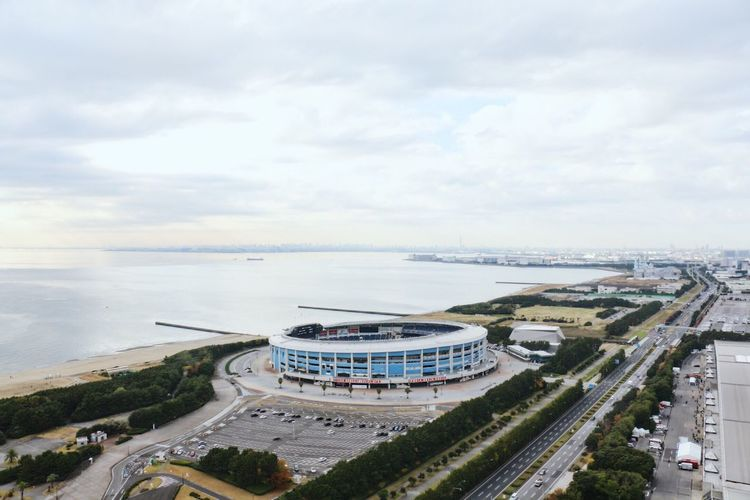 High angle view of city by sea against sky