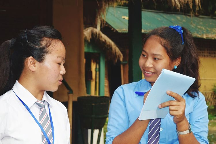 Teenage Girl With Friend Wearing School Uniforms Writing On Note Pad