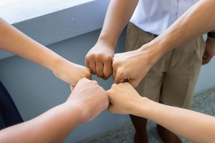 Cropped image of friends giving fist bumps