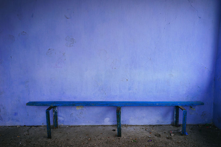 Empty bench against wall