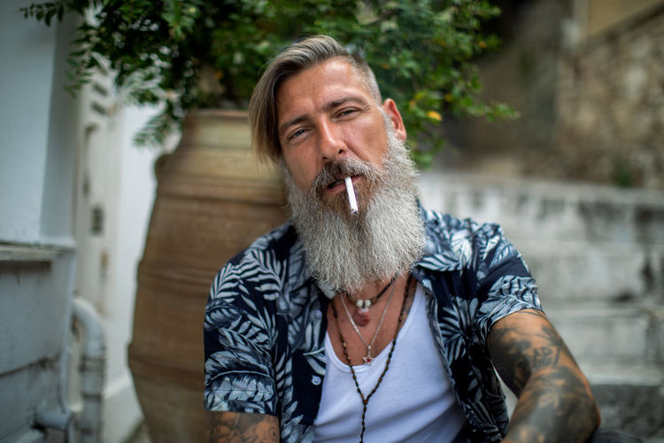 Attractive bearded man with tattoos is sitting on the stairways in the old city of athens and smoke a cigarettes One Person Facial Hair Males  Beard Portrait Adult Men Front View Waist Up Real People Lifestyles Mature Adult Headshot Casual Clothing Mature Men Leisure Activity Cigarette  Mustache Outdoors Mouth Open Contemplation Smoking Smoke - Physical Structure Bearded Stairway