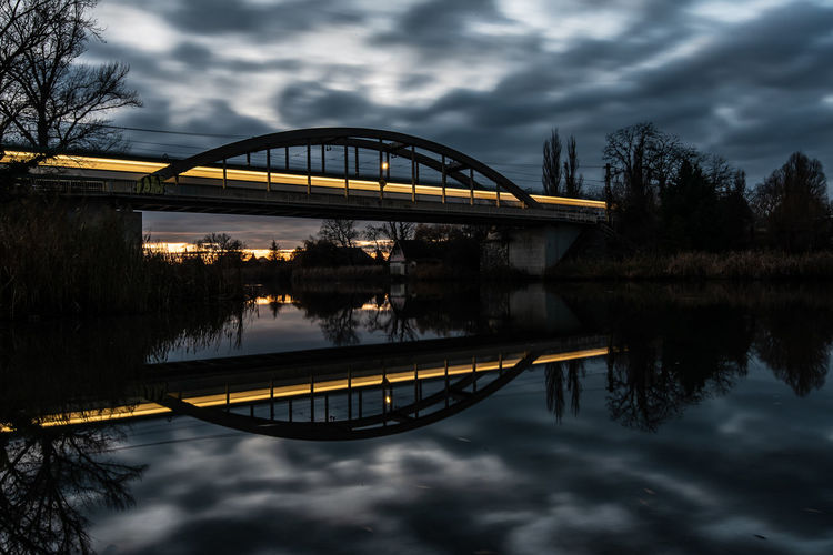 Architecture Reflection River Water Sunset Nature Sky Dusk Bridge Tree Sundown Outdoors Transportation Waterfront Connection No People Riverbank Arch Bridge Cloud - Sky Building Exterior Built Structure Bridge - Man Made Structure Plant Illuminated Train