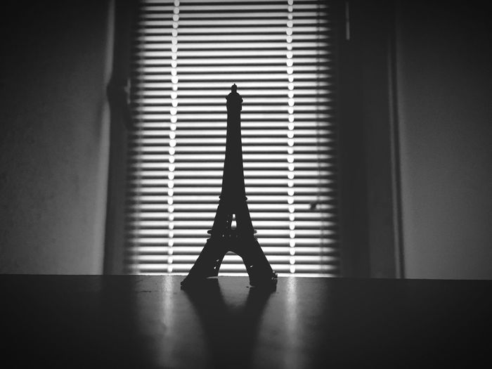 Close-up of eiffel tower souvenir on table against window blinds
