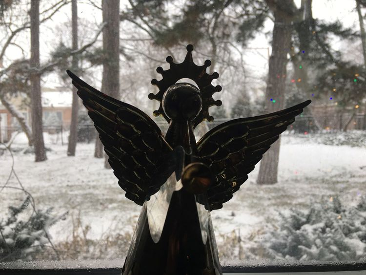 Metal angel sits in a snowy window with Christmas tree lights reflected behind it. White Christmas Christian Serenity Angel Snow Religion Spirituality Memorial Cultures Sculpture Statue No People Outdoors Day Nature