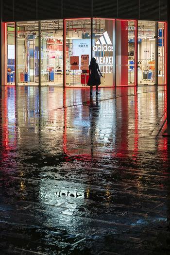 People walking on wet street during monsoon