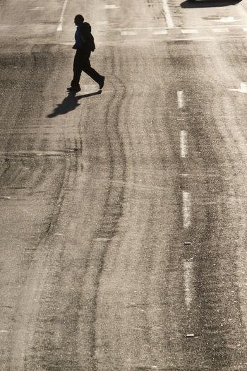 Full length of silhouette man walking on road