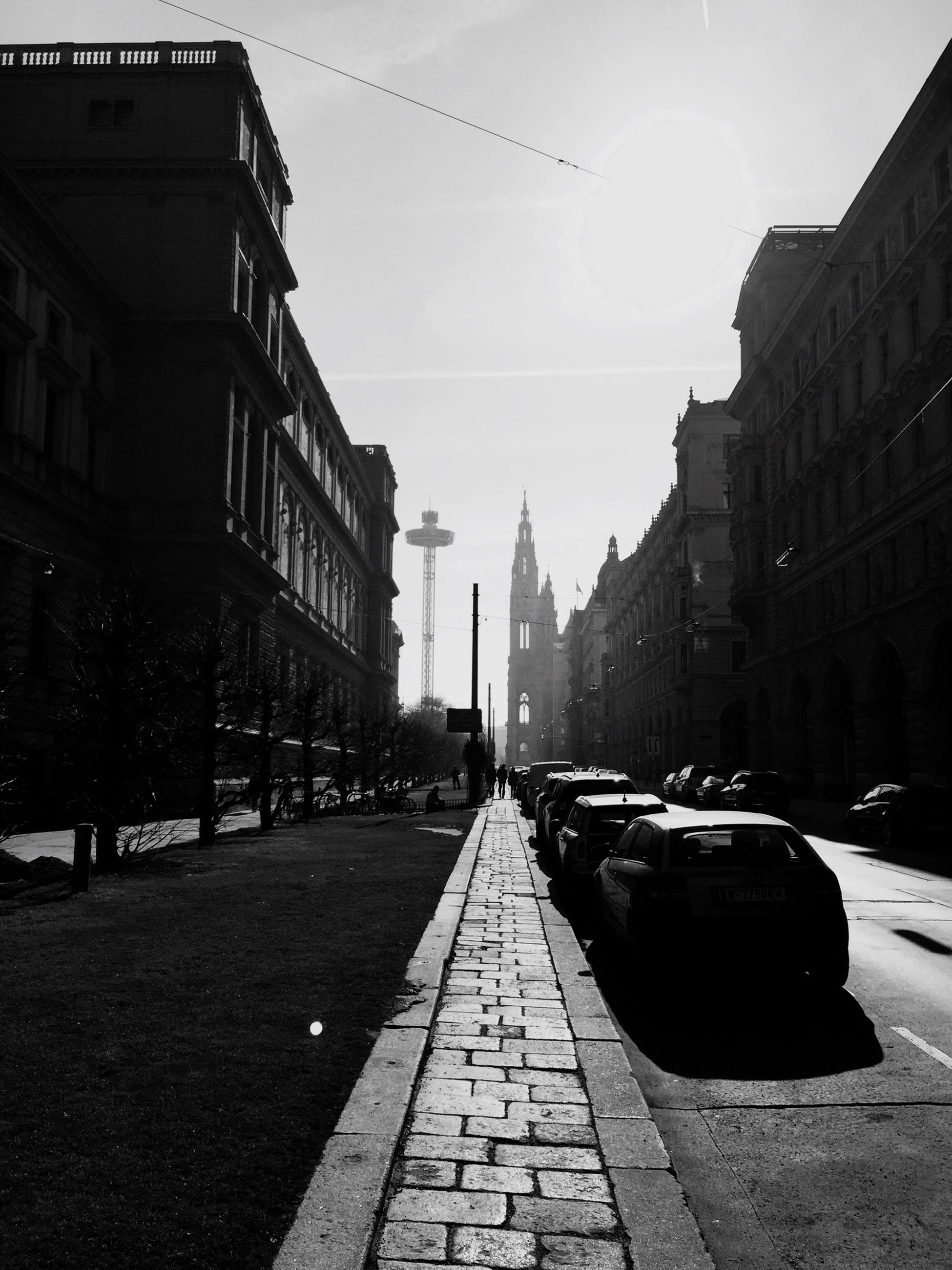 building exterior, architecture, built structure, city, street, the way forward, transportation, sky, cobblestone, car, diminishing perspective, building, city life, incidental people, city street, road, vanishing point, travel, travel destinations, sunlight