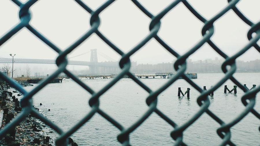 Williamsburg bridge and manhattan bridge from behind a fence on brooklyn shore