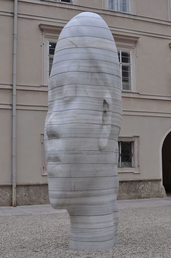 Rear view of statue against building in city
