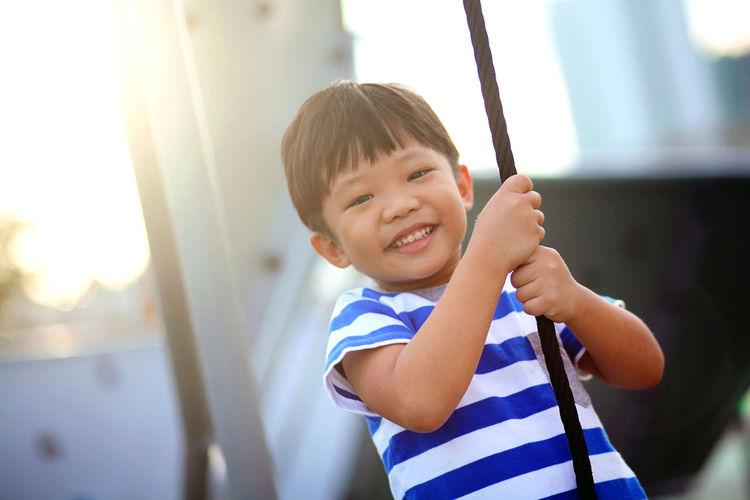 Portrait of smiling boy swinging on swing