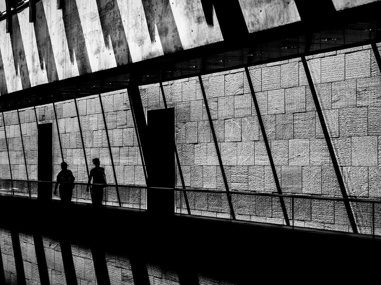 architecture, real people, built structure, silhouette, railing, walking, men, indoors, group of people, building, lifestyles, people, day, women, high angle view, shadow, leisure activity, wall - building feature, adult