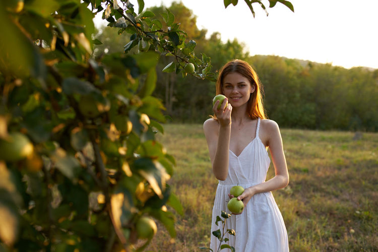 Happy woman standing by tree against plants