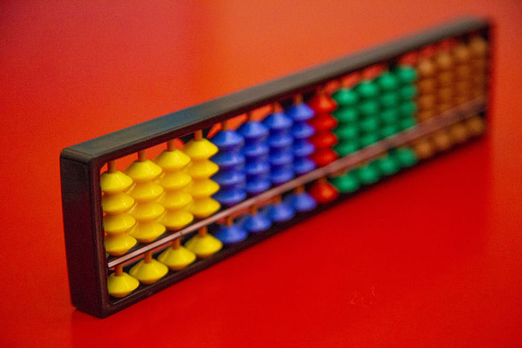 Close-up of abacus on red table
