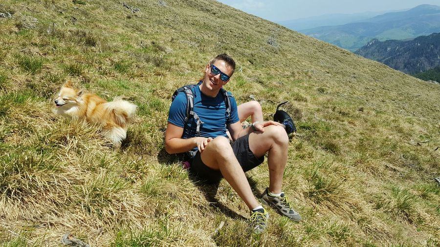 Full length of man sitting with dogs on mountain
