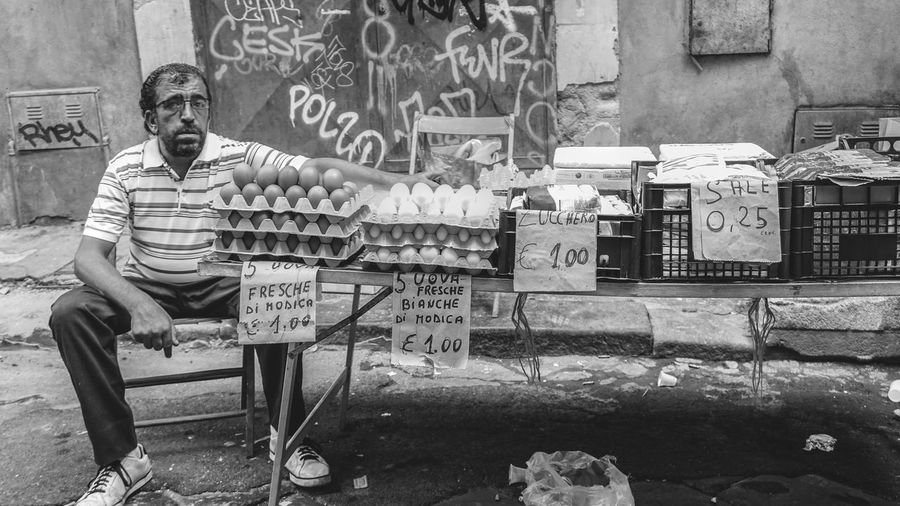 market vendor, eggs, Catania, Sicily, Italy Looking At Camera Real People One Person Sitting Eggs Market Market Stall Black And White Streetphotography Street Photography Sicily Catania Travel Travel Destinations Portrait Chair Seat Front View Casual Clothing