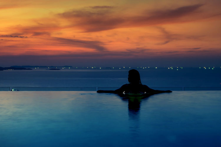 Rear view of silhouette woman in infinity pool against sea during sunset
