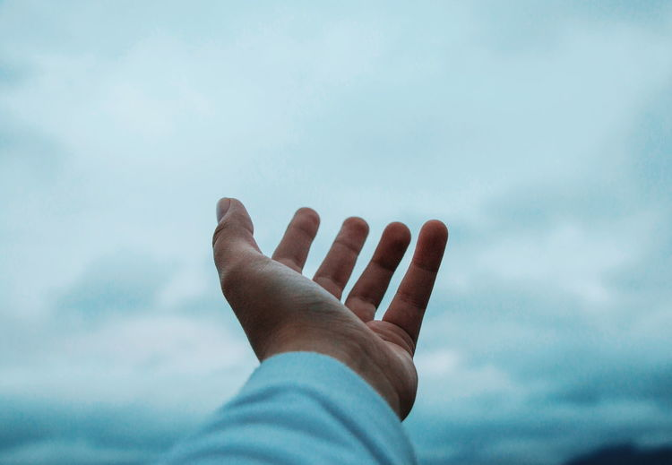 Cropped hand of person gesturing against sky