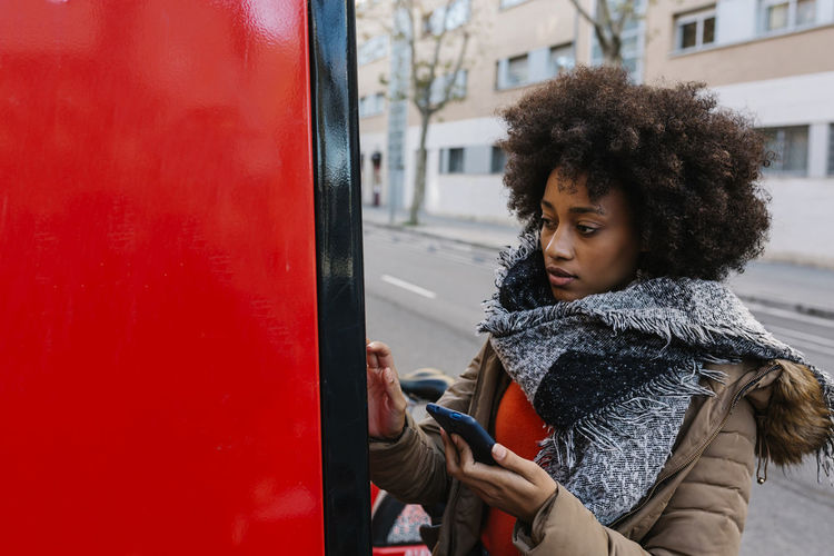 Young woman looking down while standing in bus