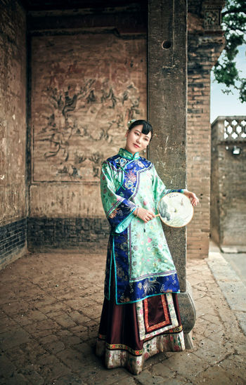 Smiling Young Woman With Hand Fan Standing At Old Building