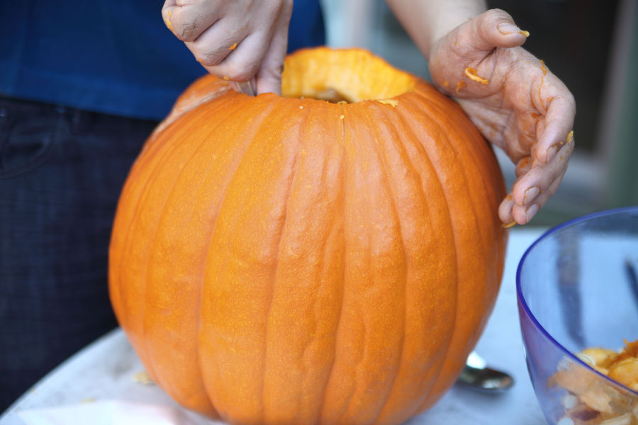 Hollowing out a Halloween pumpkin before carving American Culture Autumn Close-up Craft Fall Activities Fingers Halloween Hands Holiday Holiday Preparation Making Jack O' Lantern Man Messy Natural Light October One Person Orange Color Outdoors Pumpkin Seasonal Textures